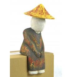 Statue personnage asiatique assis rebord étagère. Déco ethnique chic.