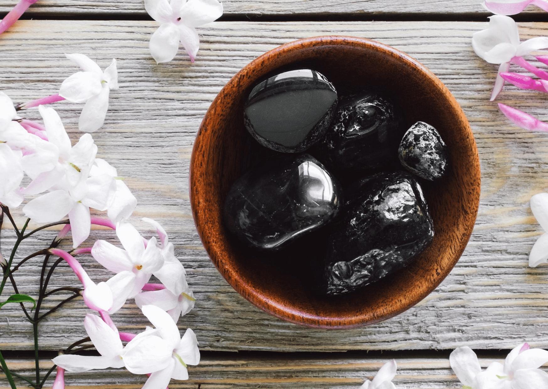 pierres obsidienne dans bol marron entouré de fleurs pierre noire