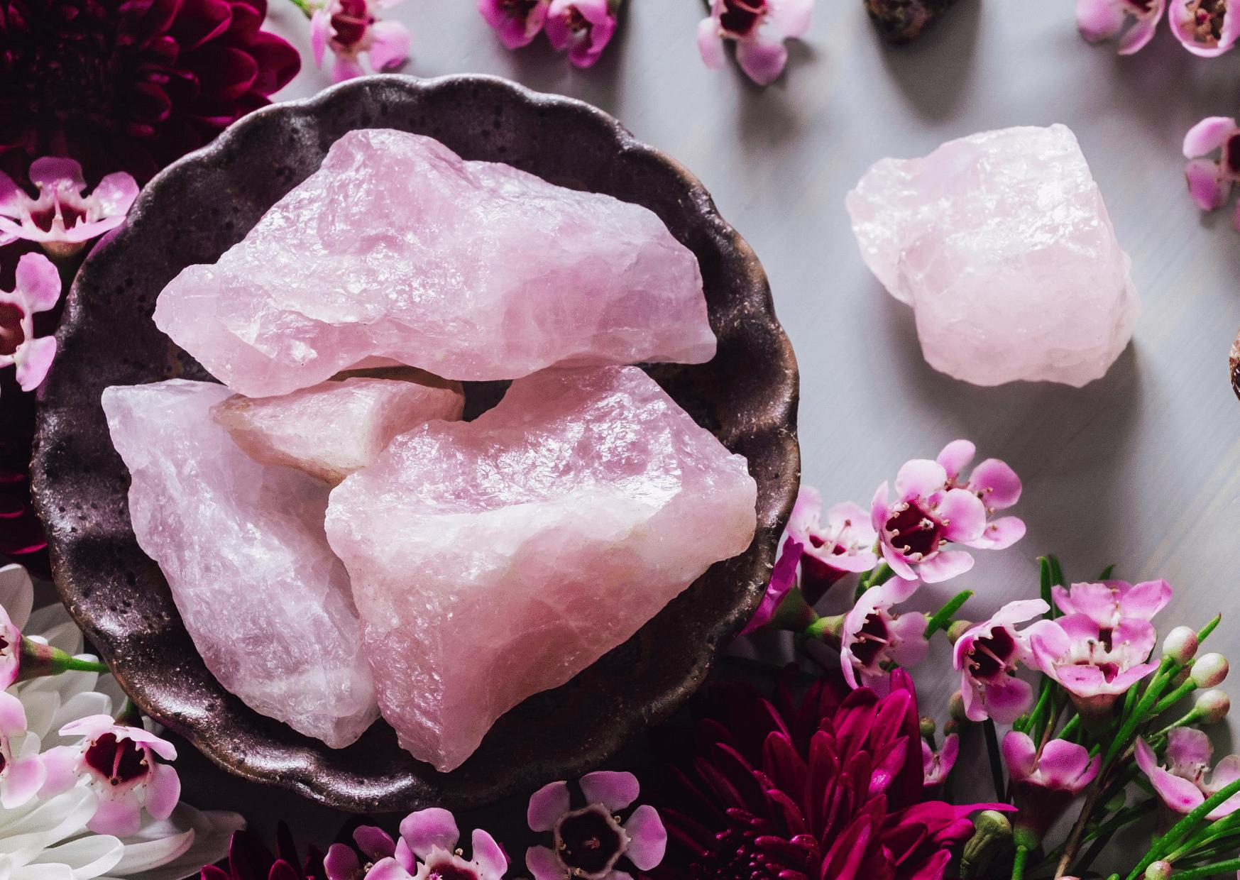 quartz rose dans bol marron entouré de fleurs pierre brute rose